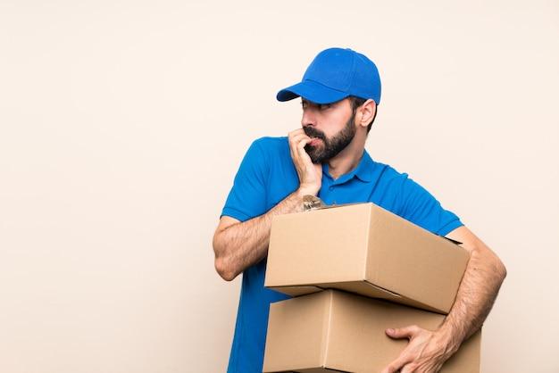 Uomo di consegna con la barba nervoso e spaventato mettendo le mani alla bocca