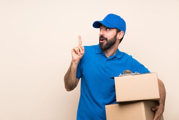 Uomo di consegna con la barba sopra il muro isolato con l'intenzione di realizzare la soluzione mentre si solleva un dito