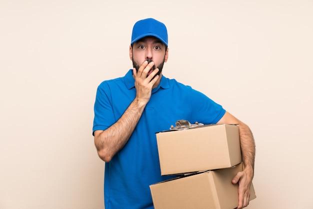 Uomo di consegna con la barba sopra il muro isolato sorpreso e scioccato mentre sembra giusto