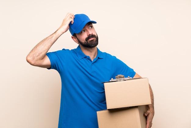 Uomo di consegna con la barba sopra isolato avendo dubbi mentre grattando la testa