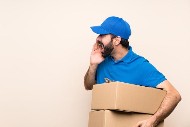 Uomo di consegna con la barba sopra isolato gridando con la bocca spalancata sul lato