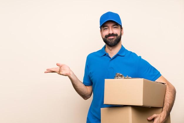 Uomo di consegna con la barba sopra le mani allungate isolate sul lato per invitare a venire