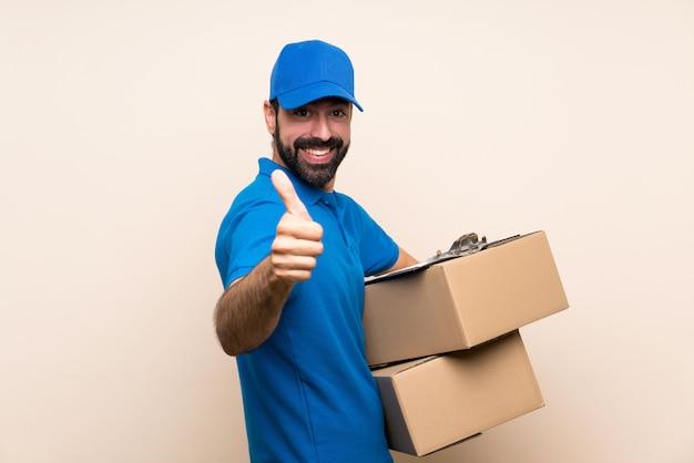 Uomo di consegna con la barba sul muro isolato con il pollice in alto perché è successo qualcosa di buono