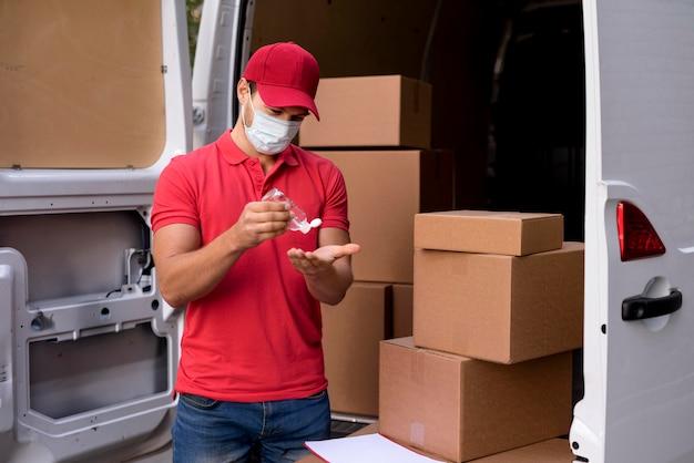 Uomo di consegna con maschera utilizzando disinfettante per le mani