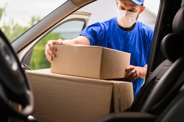 Uomo di consegna con scatole di trasporto maschera facciale