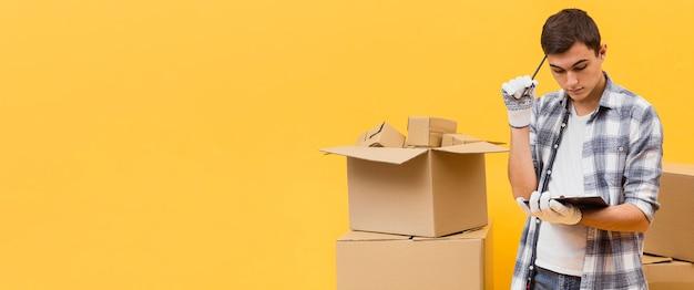 Uomo di consegna copia-spazio che controlla la lista dei pacchetti