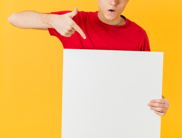 Uomo di consegna del primo piano che indica al foglio di carta bianco