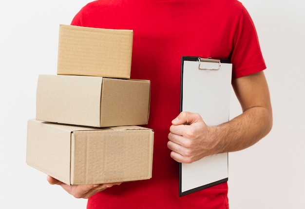 Uomo di consegna del primo piano con appunti e pacchetti