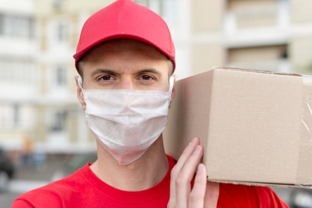 Uomo di consegna del primo piano con la maschera