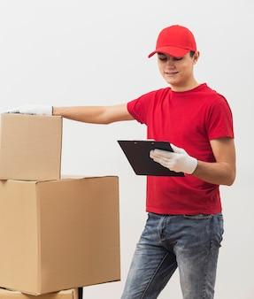 Uomo di consegna dell'angolo alto che controlla i pacchetti