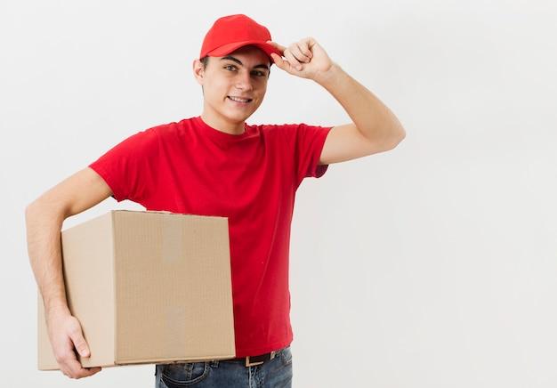 Uomo di consegna dell'angolo alto che trasporta grande pacchetto