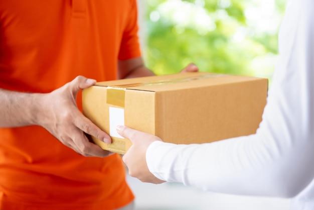 Uomo di consegna di servizio di corriere che dà la cassetta dei pacchi al cliente
