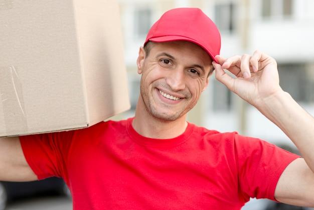 Uomo di consegna di smiley che fa il suo lavoro