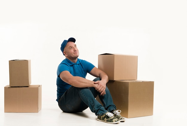 Uomo di consegna di smiley che posa con le scatole di cartone