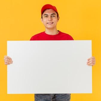 Uomo di consegna di smiley che tiene foglio di carta bianco