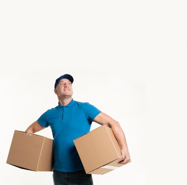 Uomo di consegna di smiley con scatole di cartone in armi e copia spazio