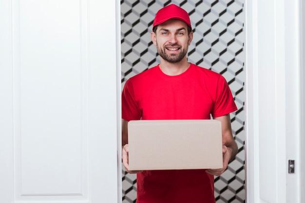 Uomo di consegna di smiley di vista frontale che indossa uniforme rossa
