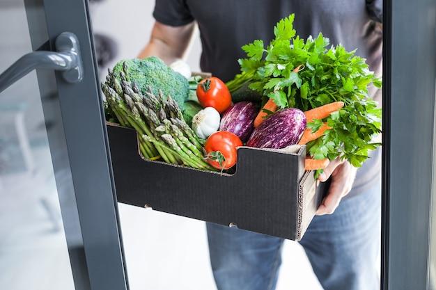 Uomo di consegna di verdure e verdure organiche fresche
