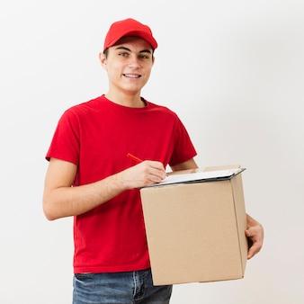 Uomo di consegna di vista frontale che firma per il pacchetto di consegna