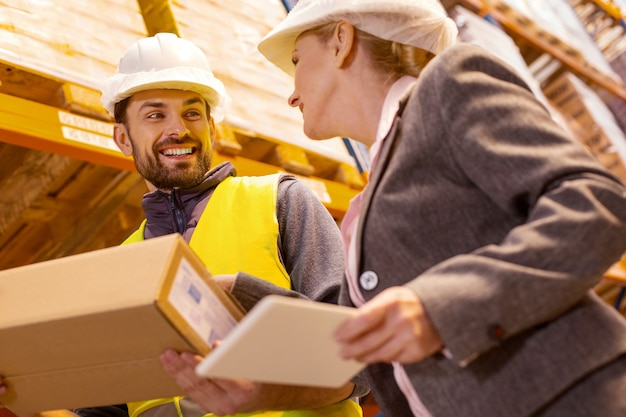 Uomo di consegna gioioso che tiene un pacchetto mentre parla con il cliente nel magazzino