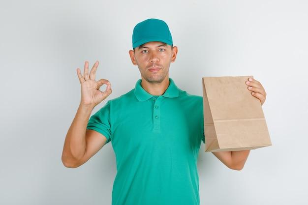 Uomo di consegna in maglietta verde e cappuccio facendo segno giusto con il sacchetto di carta