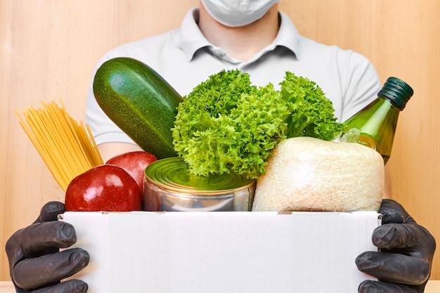 Uomo di consegna in maschera protettiva e guanti di gomma che maneggiano una scatola con vari alimenti. consegna del cibo durante la quarantena del coronavirus.