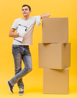 Uomo di consegna in piedi accanto a pacchi