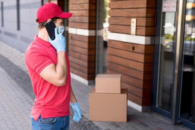 Uomo di consegna parlando al telefono