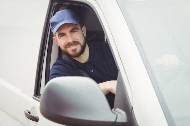 Uomo di consegna seduto nel suo furgone mentre guardando la telecamera