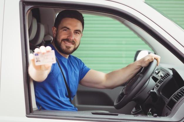 Uomo di consegna seduto nel suo furgone mentre mostra la sua patente di guida