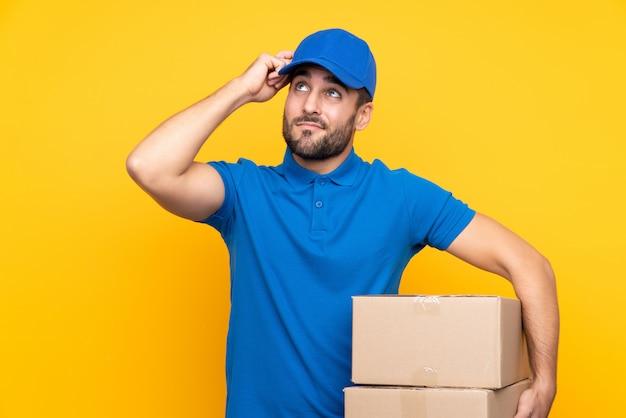 Uomo di consegna sopra giallo isolato con dubbi e con espressione faccia confusa