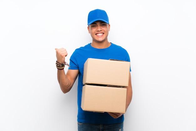Uomo di consegna sul muro bianco isolato che punta verso il lato per presentare un prodotto