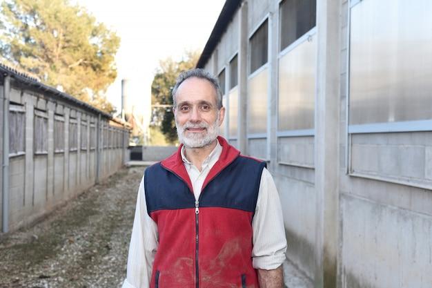 Uomo di fattoria di fronte a una fattoria degli animali
