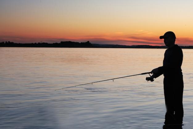 Uomo di fisher pesca con canna da spinning sulla riva di un fiume al tramonto nebbioso