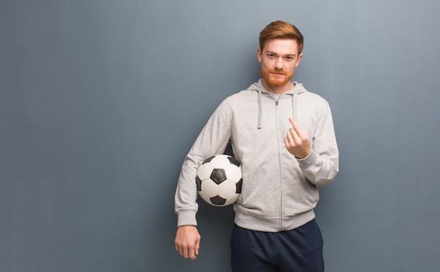 Uomo di fitness giovane rossa che invita a venire. sta tenendo un pallone da calcio.