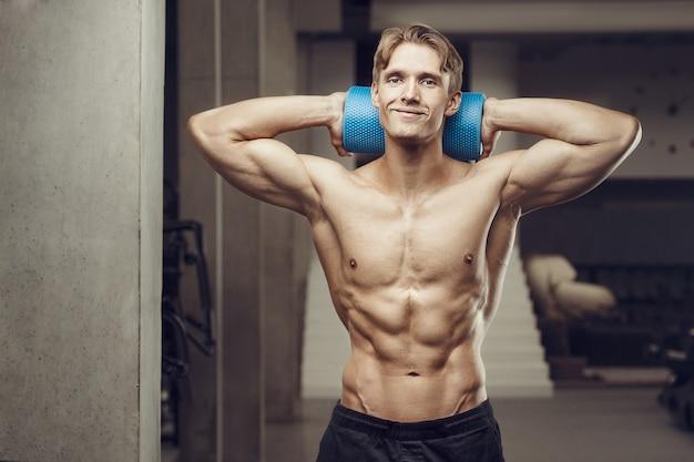 Uomo di forma fisica all'allenamento in palestra con rullo di massaggio che allunga i muscoli