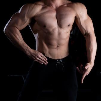 Uomo di forma fisica che mostra un pacchetto di sei