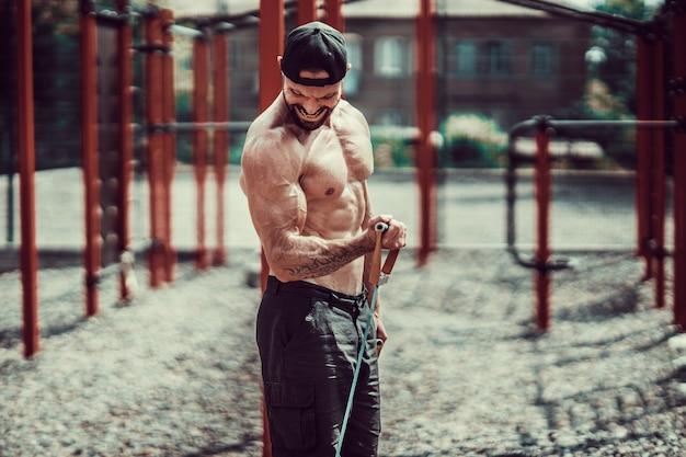 Uomo di forma fisica che si esercita con l'allungamento della banda in palestra all'aperto