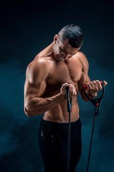 Uomo di forma fisica che si esercita con l'allungamento della banda. uomo sportivo muscolare che si esercita con l'elastico elastico. ragazzo che lavora con elastico. in forma, fitness, esercizio fisico, allenamento e stile di vita sano