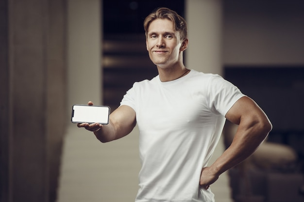 Uomo di forma fisica in palestra con il cellulare