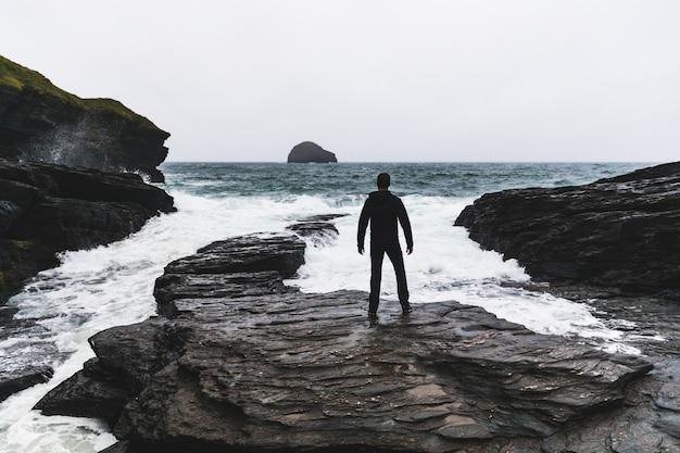 Uomo di fronte oceano e onde durante una tempesta