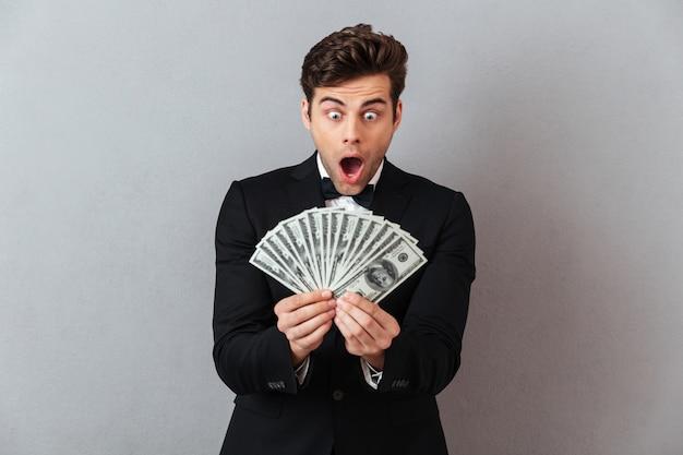 Uomo di grido in abito ufficiale in possesso di denaro.