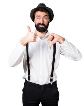 Uomo di hipster con la barba che fa buon segno cattivo
