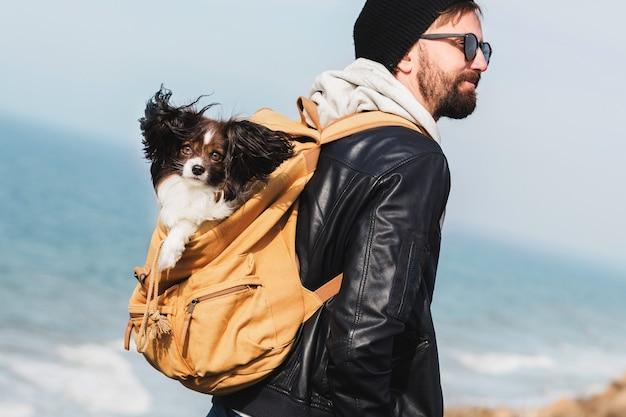 Uomo di hipster di viaggio con il cane nello zaino