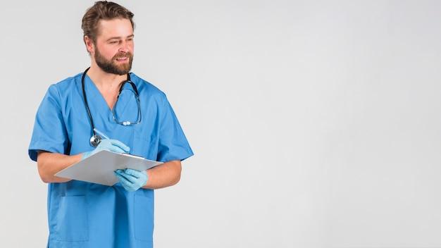 Uomo di infermiera che tiene appunti e guardando lontano