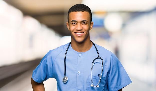Uomo di medico chirurgo in posa con le braccia all'anca e sorridente in un ospedale