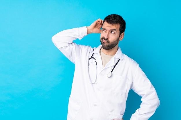 Uomo di medico sopra la parete isolata isolata