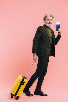 Uomo di mezza età alla moda barbuto che tiene una valigia e un passaporto gialli con un biglietto sul rosa.