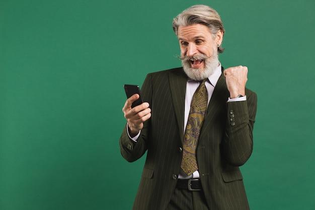 Uomo di mezza età barbuto in tuta urlando a gran voce e guardando il telefono mentre si tiene il pugno di felicità contro il muro verde