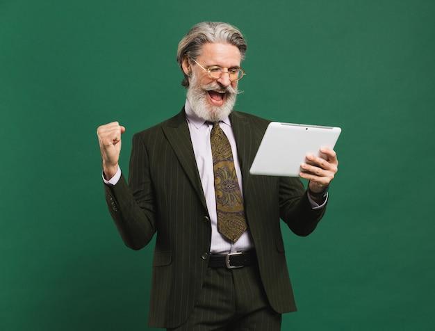 Uomo di mezza età barbuto in vestito che grida ad alta voce e che esamina compressa mentre tenendo pugno di felicità contro la parete verde